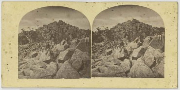 Three men sitting on boulders, Mt. Wellington